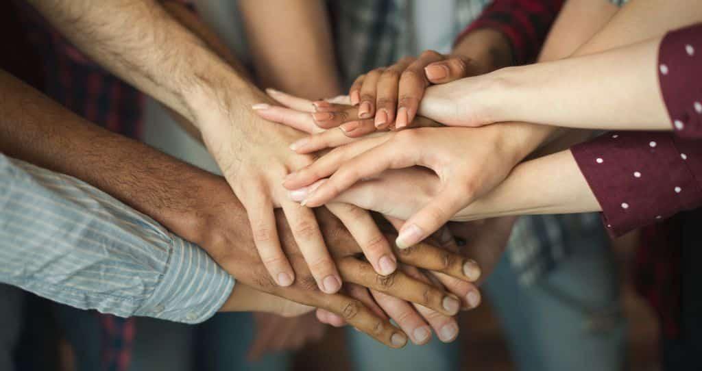 várias pessoas com as mãos juntas para representar a ideia da 2.5 ventures, uma iniciativa da FCJ Venture Builder